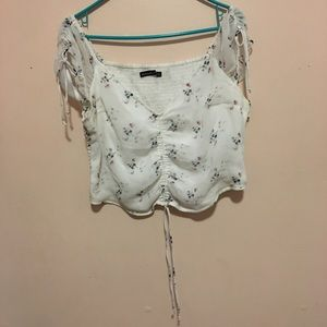 This is a white crop top with small leaf design